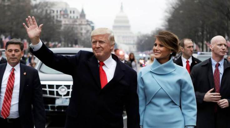 Donald Trump waves as he walks with first lady Melania Trump during the inauguration parade in Washington